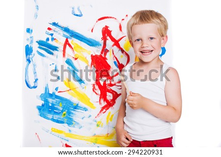 Little kid painting with paintbrush picture on easel. Education. Creativity. Studio portrait over white background - stock photo