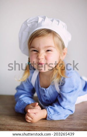 little kid play in chef at kitchen  and cook - stock photo