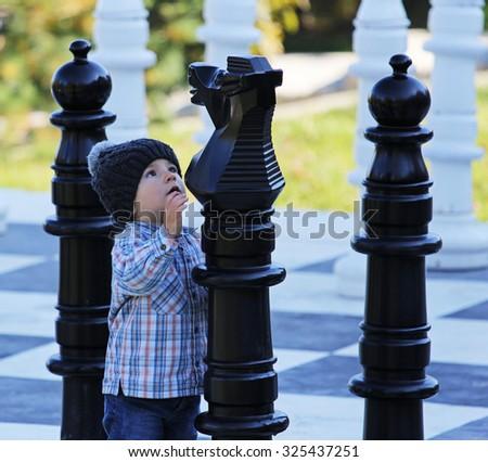 Little kid playing big chess - stock photo
