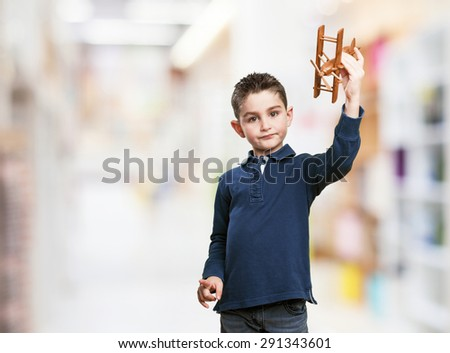 little kid playing with a biplane - stock photo