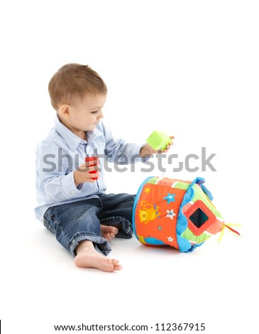Little kid playing with developmental soft toy.