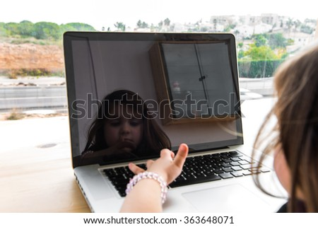 Little kid playing with laptop - stock photo
