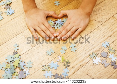 little kid playing with puzzles on wooden floor together with parent, lifestyle people concept, loving hands to each other