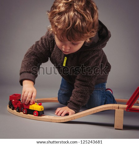 Little kid playing with train construction. Studio shot. - stock photo