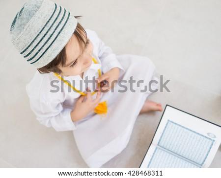 Little kid reading Koran - stock photo
