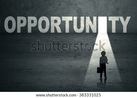 Little kid standing in front of opportunity door - stock photo