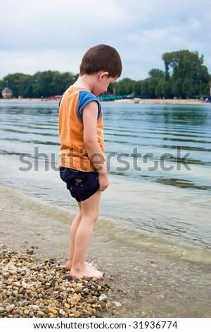 Little kid standing next to beautiful lake - stock photo