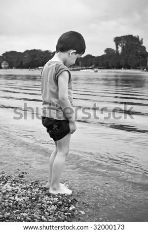 Little kid standing next to beautiful lake - B&W - stock photo