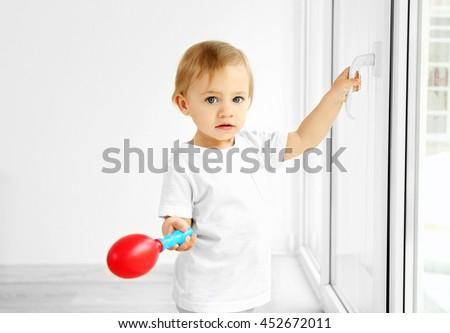Little kid standing on a windowsill - stock photo