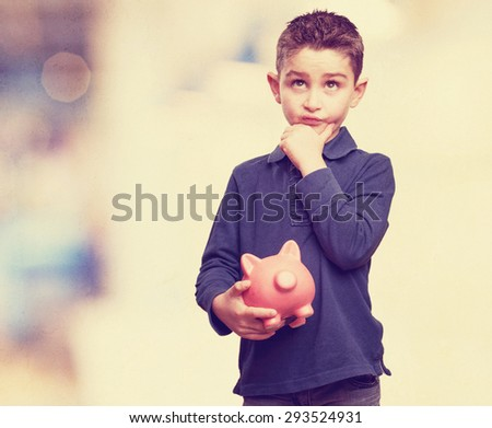little kid thinking with piggy bank - stock photo