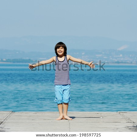 Little kid walking down the bridge on a sea summer dock - stock photo