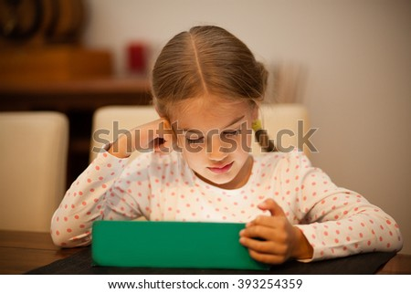 Little kid watching an electronic tablet - stock photo