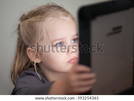 Little kid watching an electronic tablet