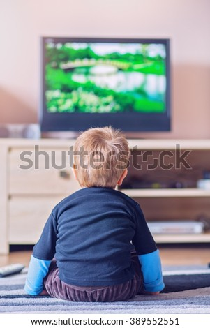 Little kid watching TV in the living room - stock photo