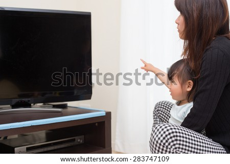 little kid watching TV program with mom