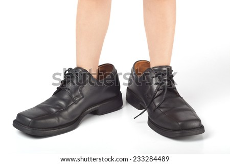 Little kid wearing adult's shoes that are too big  - stock photo