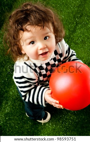 little kid with a red ball on the green grass - stock photo