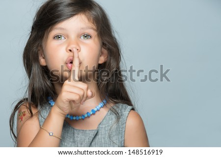 Little kid with hushing gesture and great green eyes - stock photo