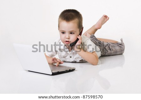 little kid with laptop and mobile phone - stock photo