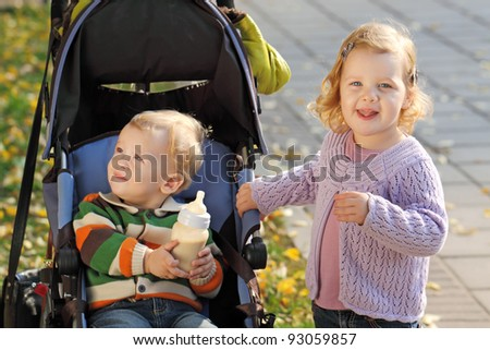 Little kids - brother and sister for a walk in the autumn park