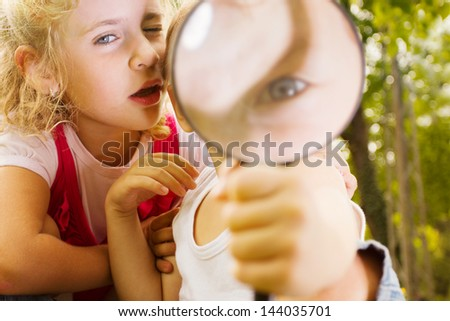 Little kids exploring nature by magnifier - stock photo