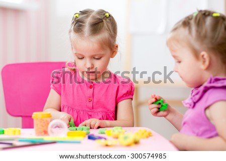 Little kids girls creating from play dough - stock photo