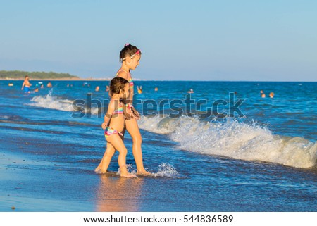 Little kids go to swim in sea water at the beach.