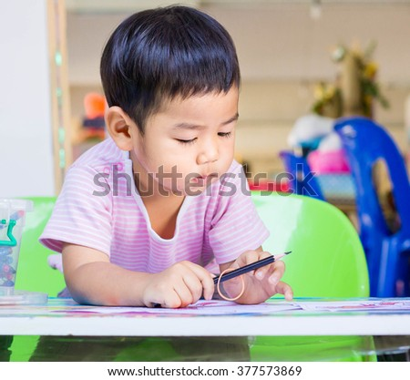 Little Kids in Asia, focusing on drawing on white paper. - stock photo