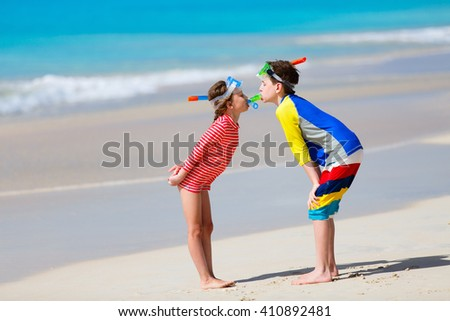 Little kids in rash guards for sun protection with snorkeling equipment on tropical beach having fun during summer vacation