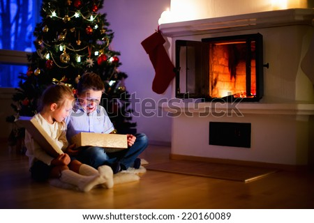Little kids opening presents next to the tree and fireplace in a cozy home celebrating Christmas - stock photo