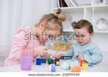 little kids  painting eggs for Easter - stock photo