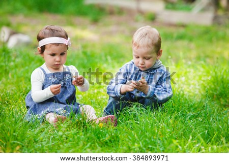 Little kids play outdoors on the grass