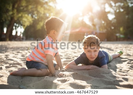 little kids play with sand on beach; happy brothers smiling and sitting on ground;