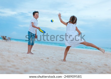 Little kids playing beach tennis on summer vacation - stock photo