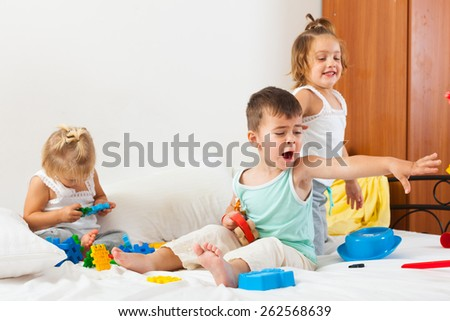 little kids playing on  white bed - stock photo