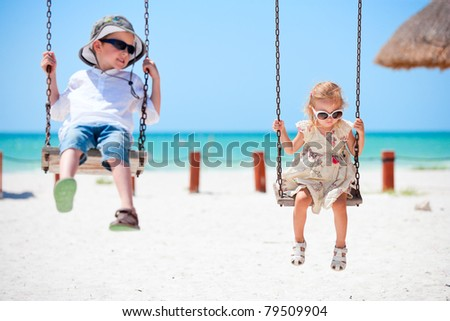 Little kids swinging with tropical beach on background - stock photo