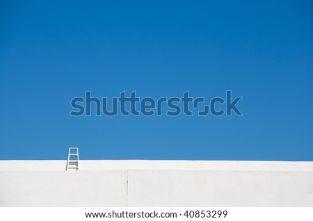 Little ladder on a bright white building reaches into a deep blue sky