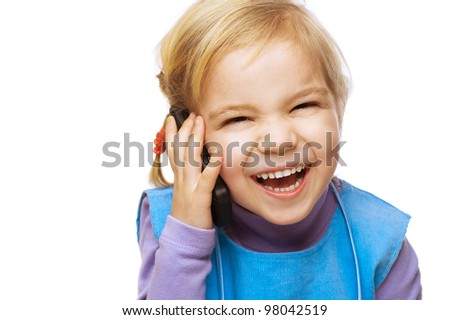 Little laughing girl in blue dress talking on cell phone, isolated on white background.