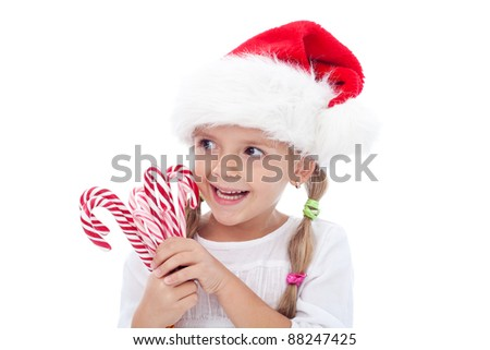 Little laughing girl with santa hat and candy canes around christmas time - isolated - stock photo
