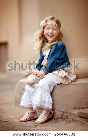 little laughing pretty girl with long blond hair are sitting with her toy in long beautiful dress and jeans jacket  - stock photo