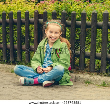 Little laughing schoolgirl  sitting on the street with her backpack - stock photo