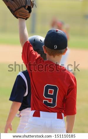 Little league baseball boy playing first base. - stock photo
