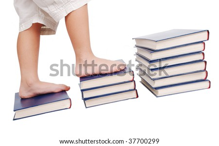 Little legs stepping on books stairs, isolated - stock photo