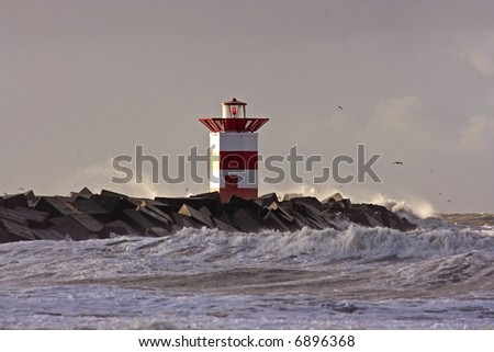 Little lighthouse at the entrance of the Scheveningen harbor in the Netherlands on a stormy day - stock photo