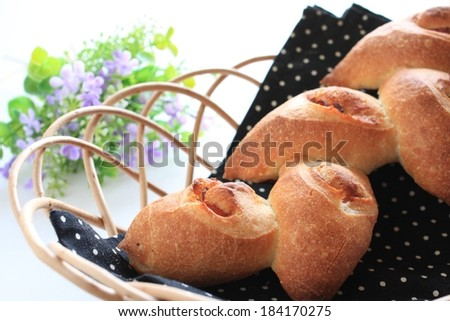 Little loaf of breads sitting on a wood basket. - stock photo