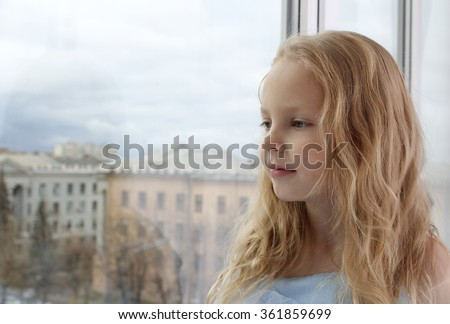 Little lonely girl looking out the window. The girl blonde. The child dreamy face. Outside, cityscape. - stock photo