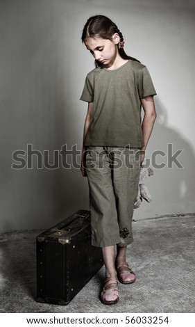Little lonely girl with suitcase - stock photo