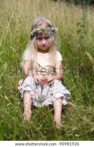 little long-haired blonde girl in wild flower wreath sitting at the meadow