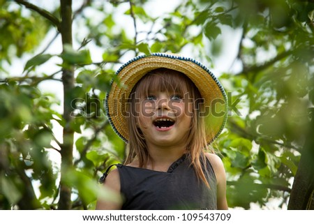 Little lovely emotional girl in a straw hat in the park. - stock photo