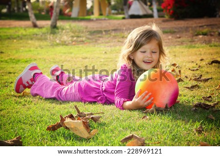 Little lovely girl playing with her ball on the grass in the park. filtered image